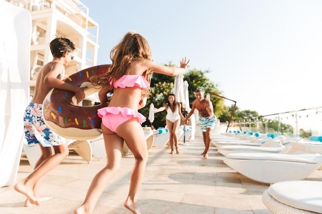 Foto de uma família caucasiana alegre com crianças descansando perto de uma piscina luxuosa e se divertindo com um anel de borracha do lado de fora do hotel
