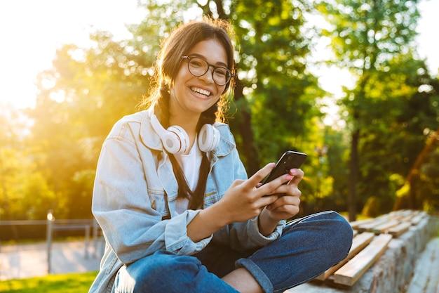 Foto de uma feliz aluna jovem bonita usando óculos, sentado ao ar livre no parque natural, usando telefone celular.