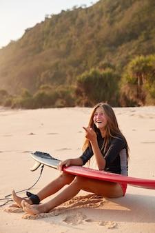 Foto de uma feliz surfista europeia em roupa de mergulho