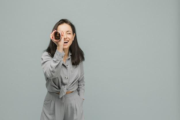 Foto de uma fofa sorridente mulher segurando uma revista como um binóculo