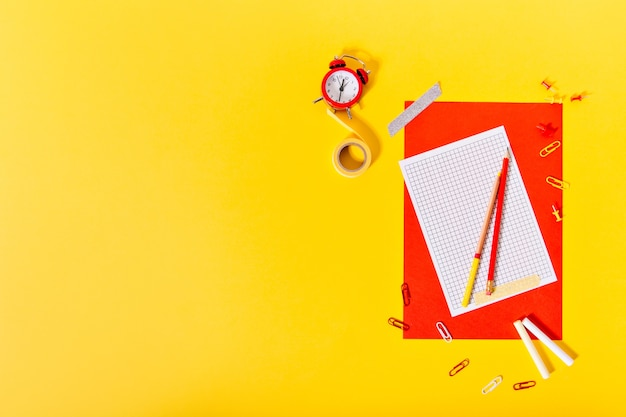 Foto de uma folha de papel vermelha, lápis, fita adesiva e despertador na parede amarela