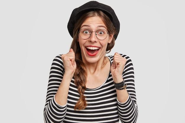 Foto de uma francesa muito feliz com os punhos cerrados e olhando para a câmera com alegria