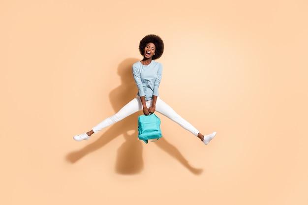 Foto de uma garota afro-americana segurando uma mochila azul, pulando com a boca aberta, espalhando as pernas isoladas em um fundo de cor bege pastel
