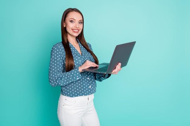 Foto de uma garota agente positiva trabalhando em um laptop usando roupas de bolinhas isoladas sobre um fundo de cor turquesa