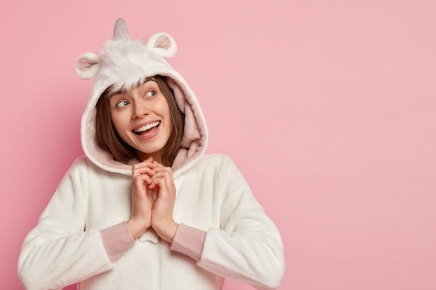 Foto de uma garota alegre e sonhadora com as mãos juntas, focada para cima com uma expressão facial alegre e pensativa