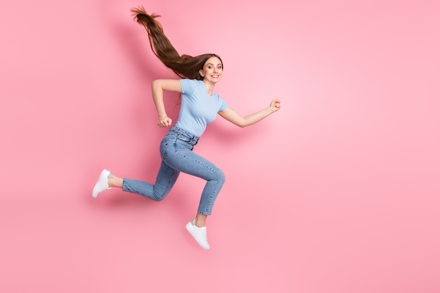 Foto de uma garota apressada pulando isolada em um fundo de cor rosa pastel
