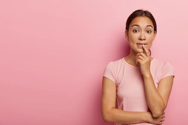 Foto de uma garota asiática confusa que morde os lábios e parece nervosa, mantém as mãos parcialmente cruzadas, usa piercing na orelha, vestida com uma camiseta casual, fica de pé na parede rosa com um espaço em branco à parte
