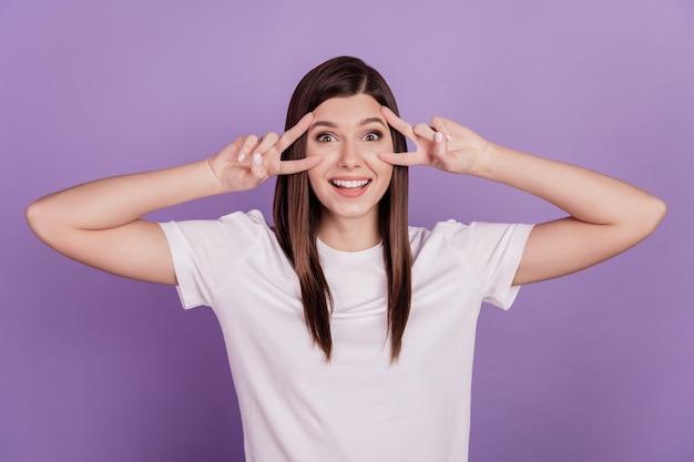 Foto de uma garota atraente mostrando um rosto com sinal de v, olhos isolados em um fundo violeta