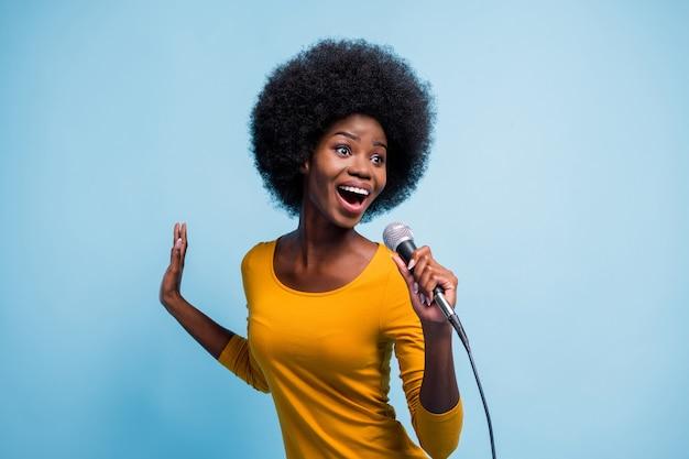 Foto de uma garota bonita de pele negra cantando no microfone e dançando no palco, isolado em um fundo de cor azul brilhante