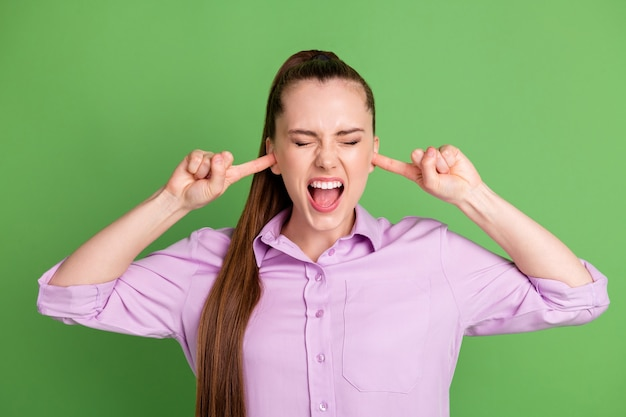 Foto de uma garota com raiva frustrada que não consegue ouvir música alta barulho fecha a capa grito do dedo indicador e usa uma camisa lilás isolada sobre o fundo de cor verde