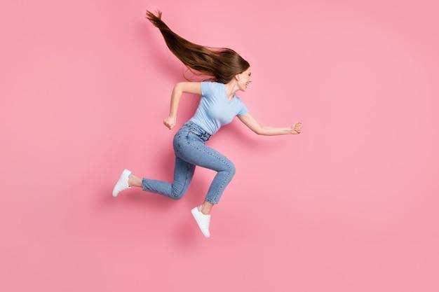 Foto de uma garota correndo pulando isolada em um fundo de cor rosa pastel