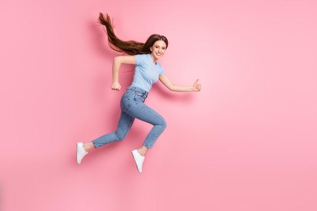 Foto de uma garota correndo pulando mostrando os polegares isolados em um fundo de cor rosa pastel