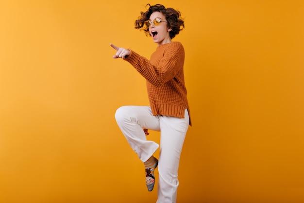 Foto de uma garota de cabelos escuros com um suéter de lã dançando no espaço laranja com um sorriso
