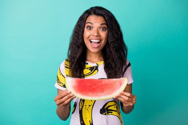 Foto de uma garota de pele escura espantada segurando uma deliciosa fatia de melancia isolada em um fundo de cor turquesa