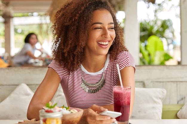 Foto de uma garota de pele escura radiante com cabelo espesso, ri e olha para o lado, usa o telefone celular para comunicação online e troca de mensagens com amigos, bebe smoothie em uma cafeteria aconchegante