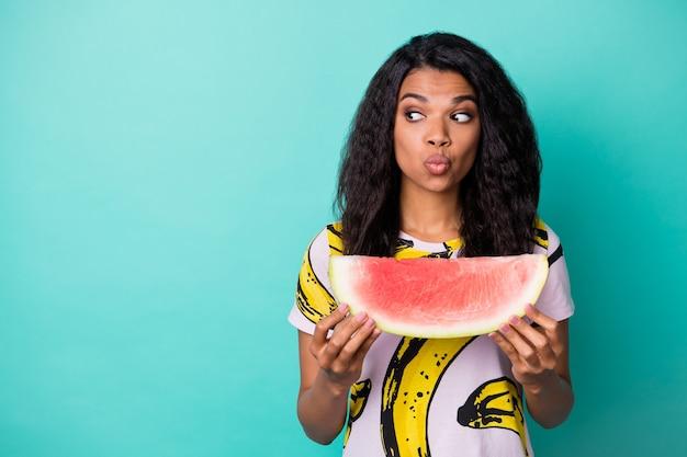 Foto de uma garota de pele muito escura olhando um espaço vazio segurar uma fatia de melancia usar uma camiseta rosa isolada sobre um fundo de cor azul-petróleo