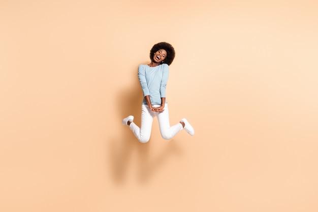 Foto de uma garota de pele negra com as duas mãos para baixo, pulando no ar, isolada em um fundo de cor bege pastel