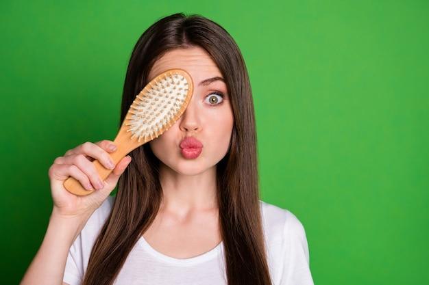 Foto de uma garota fazendo beicinho cobrindo um olho com uma escova de cabelo isolada em um fundo de cor verde vívido