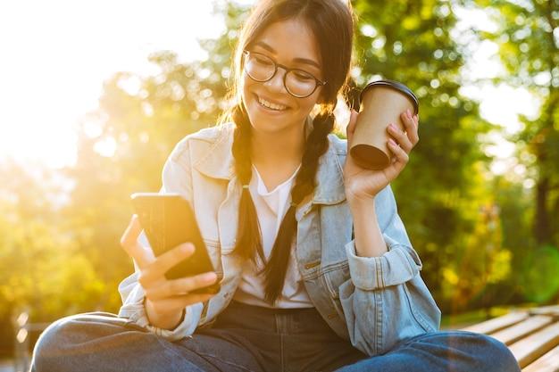 Foto de uma garota feliz bonito jovem estudante usando óculos, sentado ao ar livre no parque natural, usando telefone celular, bebendo café.
