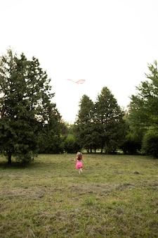 Foto de uma garota feliz se divertindo com uma pipa