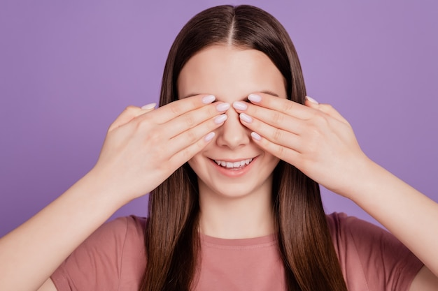 Foto de uma garota jovem e atraente de cabelo castanho com as mãos fechando os olhos da tampa isolados sobre um fundo violeta
