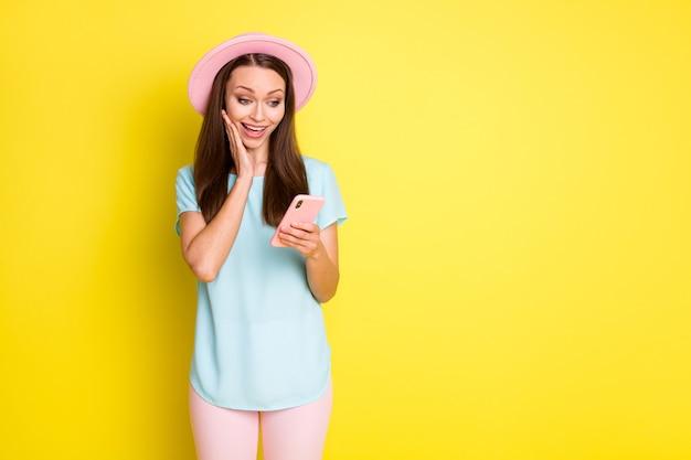 Foto de uma garota louca e surpresa, usando smartphone, impressionado, rede social, notícias, rosto, rosto, bochecha, mão, usar, rosa, azul, chapéu de sol, calças, calça, isolado, brilhante, cor, fundo