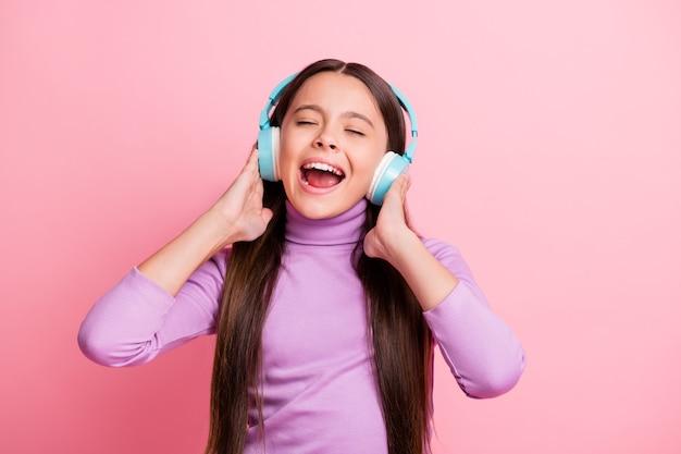 Foto de uma garota maluca curtindo ouvir música em um fone de ouvido sem fio isolado sobre um fundo de cor pastel