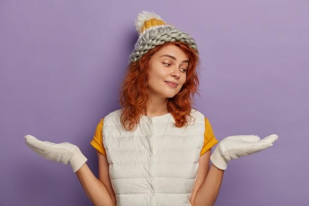 Foto de uma garota milenar com as palmas das mãos para os lados, fingindo que está segurando algo e escolhe entre dois itens, usa chapéu, luvas brancas, aproveita as férias de inverno, isolado sobre o fundo roxo