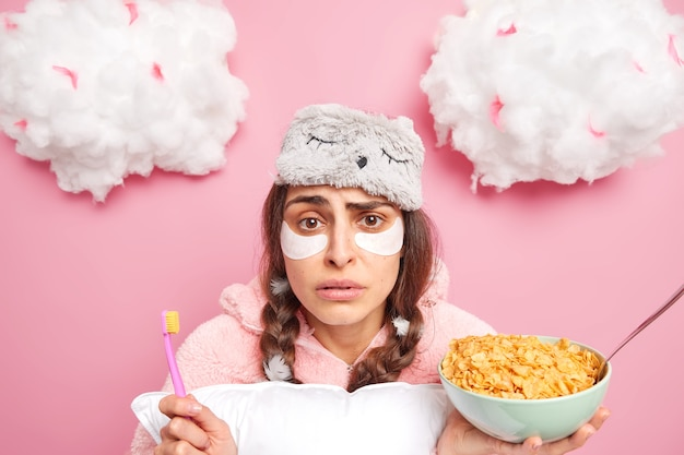 Foto de uma garota milenar perplexa escovando os dentes e tomando um café da manhã saudável
