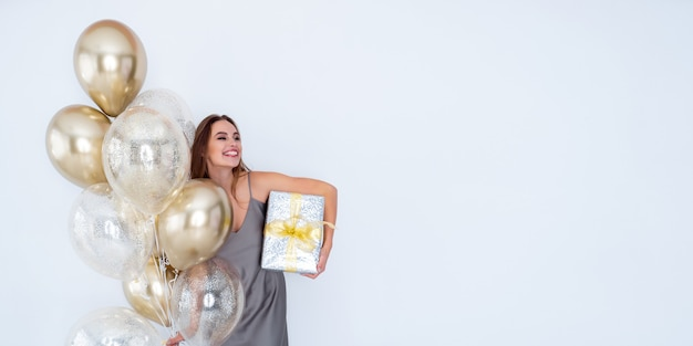 Foto de uma garota rindo segurando uma grande caixa de presente embrulhada e muitos balões de ar anúncio de celebração