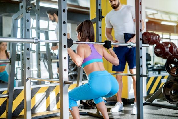 Foto de uma garota sexy forte fazendo agachamentos com barra pesada na academia enquanto seu treinador pessoal de fitness a está observando.