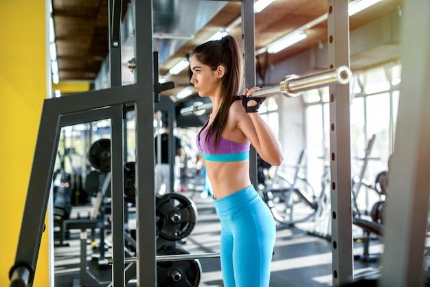 Foto de uma garota sexy forte fazendo agachamentos com barra pesada no ginásio.