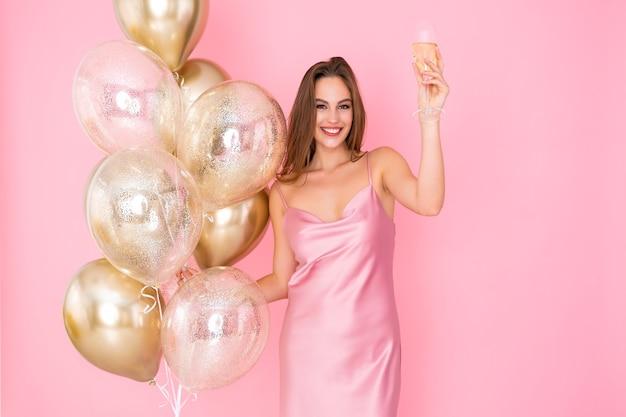 Foto de uma garota sorridente levanta uma taça de champanhe e muitos balões de ar vieram para a celebração da festa