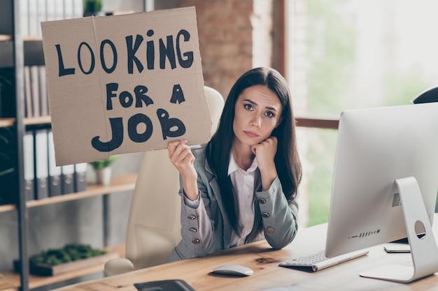 Foto de uma garota triste e frustrada. agente financeiro, comerciante, sente-se na mesa, segure um texto de papelão, procure emprego, demitiu-se da empresa crise recessão usar jaqueta no local de trabalho