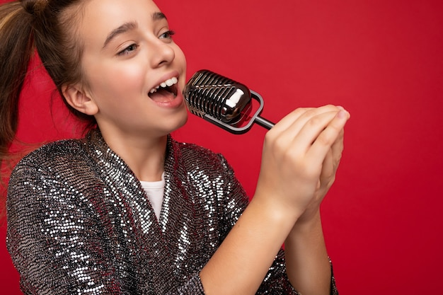 Foto de uma garotinha morena muito feliz positiva usando um vestido elegante brilhar em pé isolado sobre a parede de fundo vermelho, cantando a música para o microfone de prata, olhando para o lado.