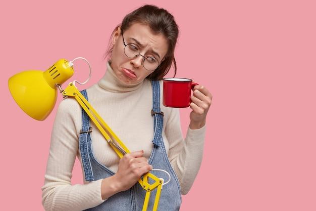 Foto de uma jovem abatida olhando com desagrado em uma caneca de bebida, segurando uma lâmpada de mesa amarela