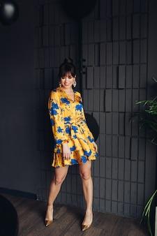 Foto de uma jovem adorável mulher branca com cabelo escuro em um vestido amarelo e azul, sapatos dourados mostra diferentes poses para a câmera
