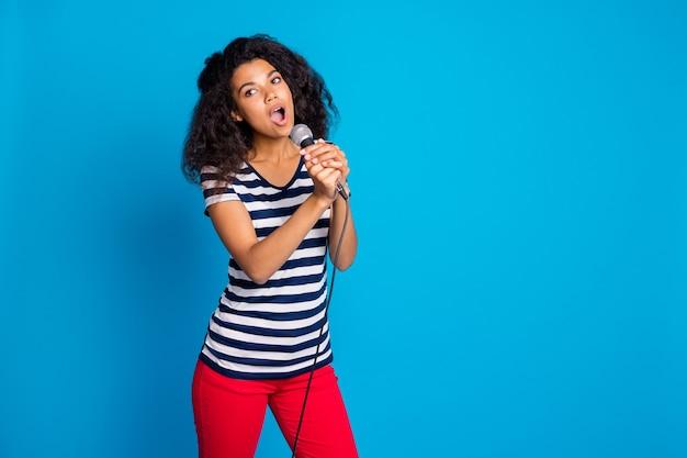 Foto de uma jovem adorável segurando um microfone representando sua música favorita
