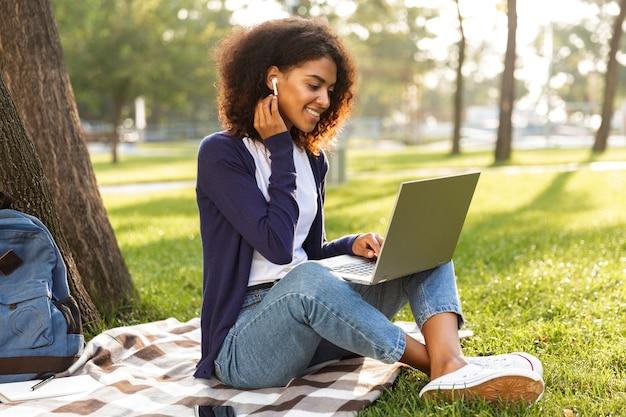Foto de uma jovem africana sentada ao ar livre no parque, usando o computador portátil, ouvindo música com fones de ouvido.