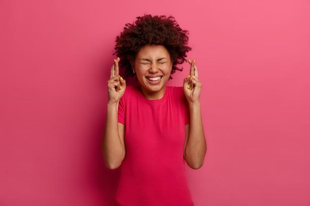 Foto de uma jovem afro-americana alegre cruza os dedos para dar sorte, antecipa para que algo de bom aconteça, espera uma grande fortuna, veste uma camiseta rosa, imagina que os sonhos se tornam realidade
