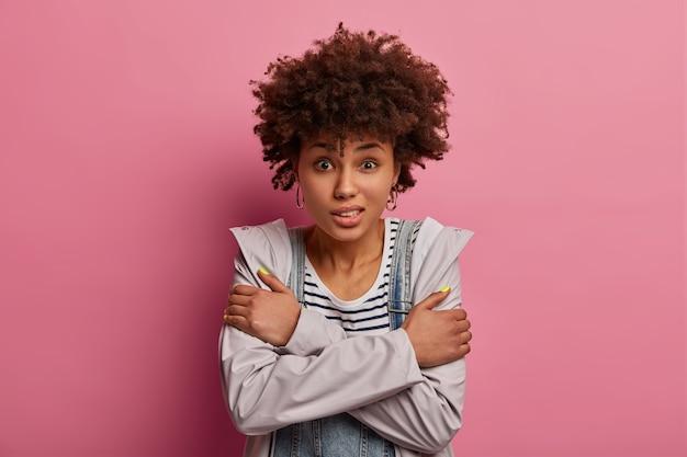 Foto de uma jovem afro-americana encaracolada cruza os braços sobre o corpo, precisa se aquecer, congelando no vento, fica insegura e assustada, sente frio e sem valor, posa contra uma parede rosa.