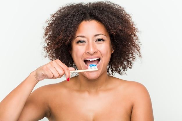 Foto de uma jovem afro-americana escovando os dentes com uma escova