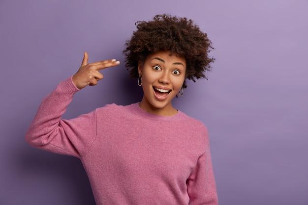 Foto de uma jovem afro-americana muito encaracolada brinca e faz o dedo com a pistola na têmpora, demonstra um gesto suicida, usa um macacão casual, isolado sobre a parede roxa