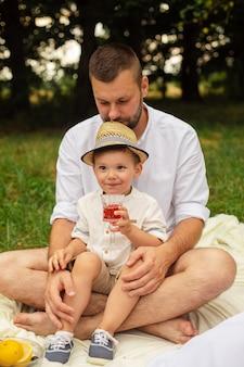 Foto de uma jovem alegre, branca, do sexo feminino e masculino segurando o filho nas mãos, sorrindo e se alegrando