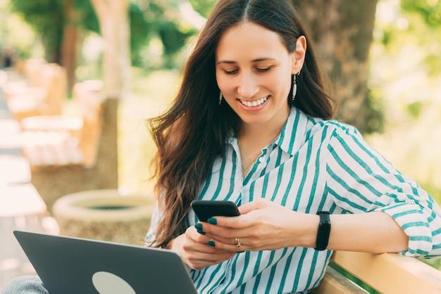 Foto de uma jovem alegre em um ambiente casual ao ar livre, digitando uma mensagem ou lendo no smartphone