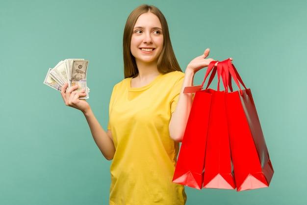 Foto de uma jovem alegre segurando um leque de dinheiro e sacolas vermelhas, isoladas no azul