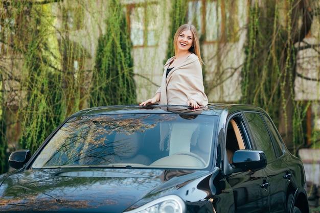 Foto de uma jovem alegre usando óculos escuros e mãos levantadas no teto solar de um carro de luxo