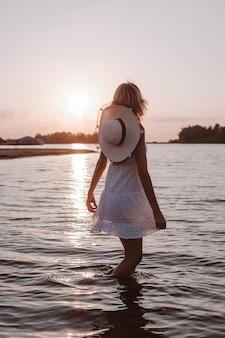 Foto de uma jovem ao pôr do sol uma bela loira esguia em um vestido branco de verão e um chapéu de palha ...