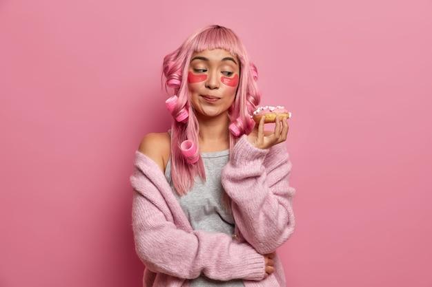 Foto de uma jovem asiática olha para um donut apetitoso, arruma o cabelo com rolos, aplica almofadas de colágeno, vestida com um suéter quente