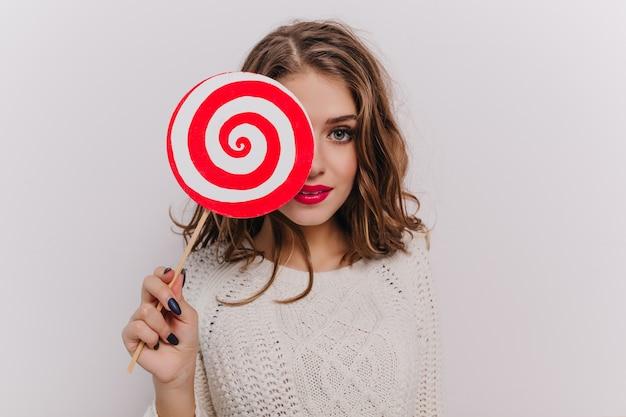 Foto de uma jovem atraente com cabelo ondulado segurando um enorme pirulito branco e vermelho